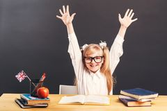 Studying in Classroom. Young pupil girl wears smart eyeglasses rise hands up learning English language with book before dark background stock image