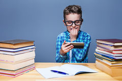 Young pupil playing on his phone in classroom Stock Photo