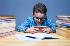 Young pupil playing on his phone in classroom Royalty Free Stock Photography