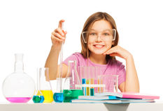 Young pupil studying chemistry in the laboratory. Young girl gathering with a pipette some blue reactant from the flask at the  laboratory Royalty Free Stock Image