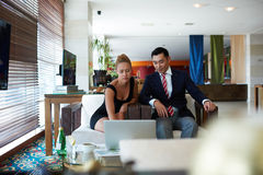 Young purposeful businessman and woman managers using net-book to prepare for the conference Royalty Free Stock Photos