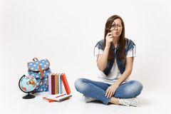 Young puzzled interested woman student holding looking on magnifying glass sitting near globe, backpack, school books stock image