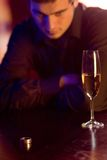 Young puzzled man with ring and champagne glass in restaurant. Focus on the ring Stock Image