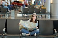 Young puzzled traveler tourist woman with crossed legs hold paper map, search route waiting in lobby hall at. International airport. Passenger traveling abroad stock image