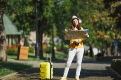 Young puzzled traveler tourist woman in yellow summer casual clothes hat with suitcase city map walking in city outdoor royalty free stock photo