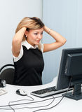 Young puzzled woman at computer Royalty Free Stock Images
