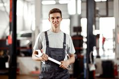 A good-looking automechanic is standing at a car repair service with a wrench in his hand stock photo