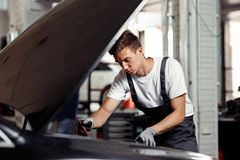 A young and qulified mechanic is doing his job at a car service: checking the results of his work stock photography