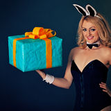Young rabbit girl with biggest gift on hand Royalty Free Stock Photos