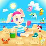 Young rabbit makes castles on the beach. Royalty Free Stock Photography