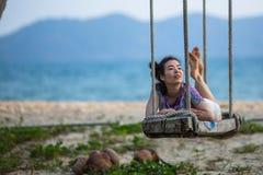 Young race woman lies on the swings on sea beach. Young mixed race woman lies on the swings on sea beach Stock Photo