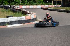 Young racer at go-kart racetrack circuit championship. Racer with a helmet competing on karting racetrack, fun youth activity.  stock images