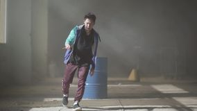 Experienced young hip-hop dancer dancing near the barrel in an abandoned building in the fog. Hip hop culture. Rehearsal. Young rapper dancing in an abandoned stock video footage