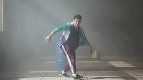 Professional young hip-hop dancer dancing near the barrel in an abandoned building in the fog. Hip hop culture. Young rapper dancing in an abandoned building stock video footage