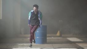 Skillful young hip-hop dancer dancing near the barrel in an abandoned building in the fog. Hip hop culture. Rehearsal. Young rapper dancing in an abandoned stock video