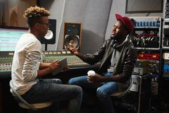 Musician and operator. Young rapper explaining sound recording operator his ideas about how his music should sound Royalty Free Stock Photo