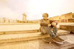 Young rasta guy outdoor on skate with a warm filter applied Stock Image