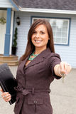 Young real estate woman handing key. Royalty Free Stock Photos