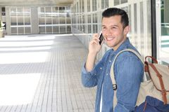 Young real looking natural man talking on his mobile phone to receive good news with copy space.  Royalty Free Stock Image