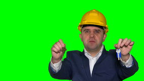 Young realtor business man with helmet hold new house construction keys. Green even chroma key background. Static closeup shot. 4K UHD stock video footage