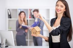 Young realtor explain lease agreement to young couple. Young realtor explain lease agreement to young couple Stock Photography