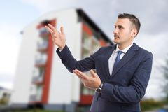 Young realtor or real estate agent holding hands in presenting g Stock Photo