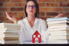 Realtor with books and house. Young realtor sitting at a table with books and house on foreground. Brick wall on background stock photos