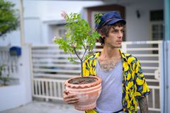 Young rebellious man thinking while holding pot of flowers outdoors royalty free stock photo