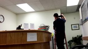 Young receptionist asking worker to fix electric appliance stock video