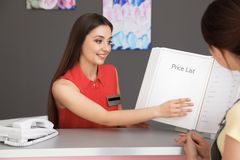 Young receptionist showing price list to client. In beauty salon stock photos