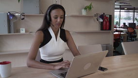 Young receptionist talking on the headset in the modern office. stock video