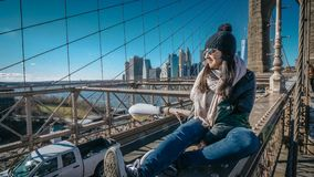 Young and reckless girl sits on the rim of Brooklyn Bridge New York stock image