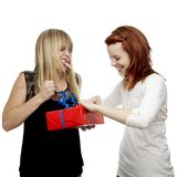 Young red and blond haired girls open gift. Young beautiful red and blond haired girls in front of white background Royalty Free Stock Photos