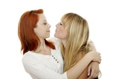 Young red and blond haired girls try to kiss Royalty Free Stock Photo