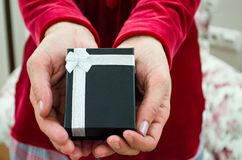 Young female is holding a black gift box with white ribbon. Young red dressed woman is holding a black fancy gift box with white ribbon Royalty Free Stock Photo