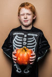 Young red hair boy holding a small pumpkin for Halloween. Studio portrait on brown background Royalty Free Stock Photos