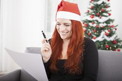 Young red hair christmas girl wish list. Young red hair girl writing a wish list and wearing a red santa hat in front of a firtree with lights and balls Royalty Free Stock Photography