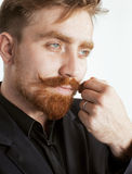 Young red hair man with beard and mustache in black suit on white background Stock Photo