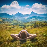Young red hair man lying on a hill. In a fresh green grass and enjoy majestic alpine mountains Stock Photos