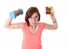 Young Red Hair Sport Woman lifting weight and cake Royalty Free Stock Image