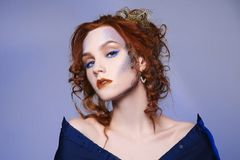 Young red hair woman with colorful make-up. Beautiful ginger girl princess with red lips and pattern Stock Photos