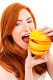 Young red hair woman with oranges in her hands. Over mouth Stock Images