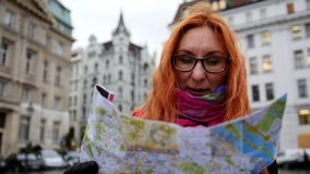Young red hair woman using city map on square in Vienna, wide angle, close up. Wide angle stock video footage