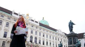 Young red hair woman using city map in Vienna, wide angle. Young attractive red-hair woman using city map in Vienna, wide angle stock footage