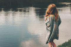 Young red hair woman walking at river alone. Wearing long cardigan Fashion Lifestyle concept emotions harmony with nature Stock Images