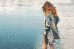 Young red hair woman walking at river alone. Wearing long cardigan Fashion Lifestyle concept and melancholy depression emotions Royalty Free Stock Photos