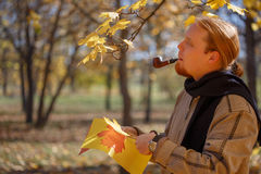 Young red-haired bearded man smokes pipe and cuts maple leaves o. Young red-haired bearded man smokes tobacco pipe and cuts maple leaves of colored paper by Stock Images