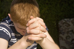 Young red haired boy has his hands folded Stock Photos
