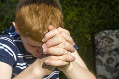 Young red haired boy has his hands folded Royalty Free Stock Photo