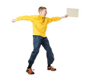Young red-haired boy in a yellow jacket jumping with arms outstretched and holds in his hand plate Royalty Free Stock Image